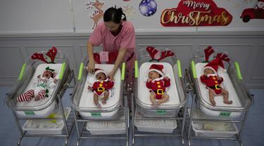 Perawat merapikan pakaian bayi yang baru lahir di Rumah Sakit Synphaet, Bangkok, Thailand, Selasa (24/12/2019). Bayi-bayi tersebut dipakaikan kostum sinterklas untuk menyambut Hari Raya Natal. (AP Photo/Sakchai Lalit)