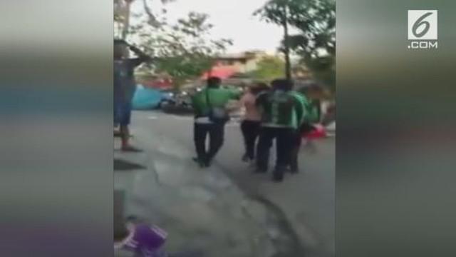 Beredar video kekerasan pada sosok mirip wanita yang dilakukan sejumpah sopir ojek online.