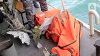 Kantong jenazah berisi puing, pakaian, dan bagian tubuh manusia dievakuasi pascajatuhnya pesawat Sriwijaya Air SJ 182 di perairan Kepulauan Seribu, Jakarta, Selasa (12/1/2021). Temuan tersebut akan dibawa dan dikumpulkan ke Pelabuhan JICT II. (Liputan6.com/Faizal Fanani)