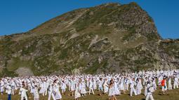 "Anggota gerakan keagamaan internasional White Brotherhood menari di puncak Gunung Rila, Bulgaria, Senin (19/8/2019). Ratusan peziarah tersebut berkumpul di puncak Gunung Rila pada 19-21 Agustus untuk menandai tahun baru ""spiritual"" mereka. (NIKOLAY DOYCHINOV/AFP)"