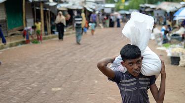 Seorang anak Rohingya membawa bantuan di kamp pengungsi Kutupalong, di Ukhia, Bangladesh pada 6 Oktober 2020. Lebih dari satu juta etnis Rohingya melarikan diri dari Myanmar dan menetap di Kutupalong yang merupakan salah satu kamp pengungsi terbesar di dunia. (Munir Uz Zaman/AFP)