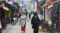Orang-orang dengan masker wajah berjalan melalui jalan perbelanjaan di Tokyo (15/10/2020). Ibukota Jepang mengonfirmasi lebih dari 280 kasus virus korona baru pada hari Kamis. (AP Photo/Hiro Komae)