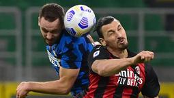 Penyerang AC Milan, Zlatan Ibrahimovic, berebut bola atas dengan bek Inter Milan, Stefan de Vrij, pada laga lanjutan Liga Italia di Stadion San Siro, Sabtu (17/10/2020) malam WIB. Dalam laga Derby Della Madonnina ini, AC Milan menang 2-1 atas Inter Milan. (AFP/Miguel Medina)