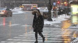 Seorang wanita melintasi Jalan Walker Chicago selama badai salju, Kamis (4/2/2021).  Total salju mengantarkan suhu di bawah titik beku di belakangnya di wilayah Chicago yang lebih luas. (AP Photo/Shafkat Anowar)