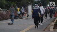 Pejalan kaki menggunakan masker di trotoar Jalan Jenderal Sudirman, Jakarta, Rabu (27/5/2020). Pemerintah akan mengerahkan personel TNI/Polri guna memastikan masyarakat menerapkan protokol kesehatan diantaranya menggunakan masker, jaga jarak, dan hindari kerumunan. (Liputan6.com/Helmi Fithriansyah)