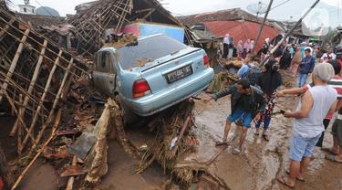 Warga menyaksikan mobil yang rusak usai banjir bandang melanda Kampung Cibuntu, Desa Pasawahan, Kecamatan Cicurug, Sukabumi, Jawa Barat, Selasa (22/9/2020). Data sementara puluhan bangunan rusak berat, 12 rumah hanyut, dan dua korban hilang masih dicari. (merdeka.com/Arie Basuki)