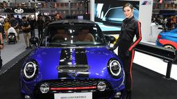 Model berpose di samping convertible Mini S 2018 selama Thailand International Motor Expo di Bangkok (29/11). Pameran ini menampilkan peserta dari 36 pembuat dari 9 negara plus 23 merek sepeda motor dari 7 negara. (AFP Photo/Lillian Suwanrumpha)