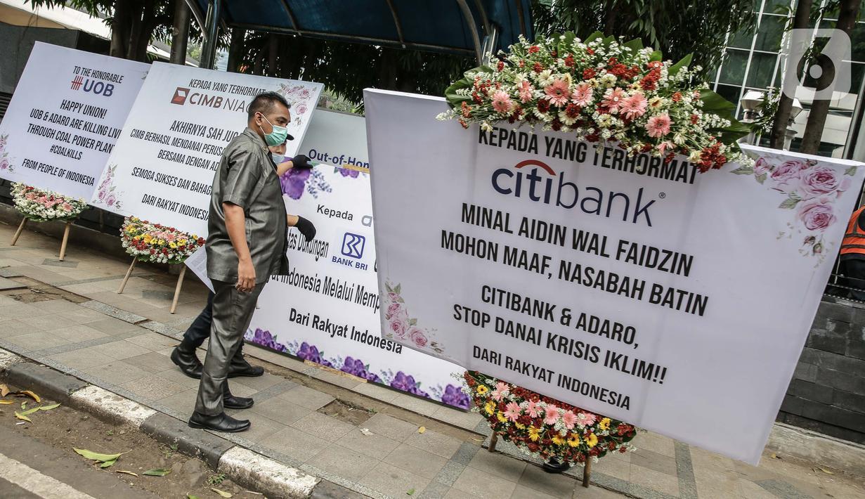 Security menurunkan karangan bunga di depan Kantor Adaro, Jakarta, Senin (3/5/2021). Gerakan Extinction Rebellion Indonesia mengirim karangan bunga yang ditujukan kepada sindikasi perbankan pemberi pinjaman dan Adaro. (Liputan6.com/Faizal Fanani)