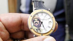Seorang penjual menunjukan jam tangan yang bergambar mantan Presiden Irak, Saddam Hussein di Baghdad, Irak (28/12). Pada 5 November 2006 Hakim Ketua Rauf Rasheed Abdel Rahman menjatuhkan hukuman mati kepada Saddam Hussein. (AFP/Sabah Arar)
