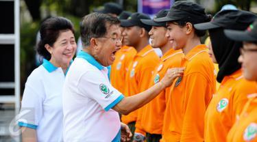 Wakil Presiden Jusuf Kalla didamping Menteri Kesehatan Nila Djuwita F. Moeloek saat menyematkan pin pada peserta jalan sehat saat Puncak Hari Kesehatan Nasional Ke-51 di Silang Monas, Jakarta, Minggu (6/12/2015). (Liputan6.com/Faizal Fanani)