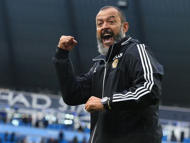 Pelatih Wolverhampton Wanderers, Nuno Espirito Santo menyapa para suporter saat berselebrasi usai pertandingan melawan Manchester City pada pertandingan lanjutan Liga Inggris di Stadion Etihad (6/10/2019). Wolverhampton menang 2-0 atas Manchester City. (AFP Photo/Lindsey Parnaby)