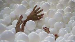 Tampak tangan – tangan para karyawan saat bersantai dan bermain di kolam bola yang ada di kantor SoHo, New York City, Selasa (25/8/2015). Tempat ini juga dibuka untuk umum dari 21 Agustus sampai 21 September. (REUTERS/Mike Segar)