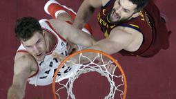 Pemain Toronto Raptors, Jakob Poeltl (kiri) melakukan layup saat diadang pemain Cleveland Cavaliers, Kevin Love pada lanjutan NBA basketball game di Quicken Loans Arena, (21/3/2018) Cleveland. Cavs menang 132-129. (AP/Tony Dejak)