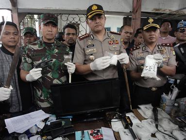 Kapolres Jakarta Barat Kombes Pol Hengki Haryadi didampingi Dandim 0503 Jakbar Letkol Kav Andre Henry Masengi menunjukkan barang bukti narkoba usai melakukan penggerebekan di Kampung Ambon, Cengkareng, Jakarta, Rabu (24/1). (Liputan6.com/Arya Manggala)