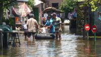 Ban bekas yang difungsikan sebagai perahu karet menjadi andalan untuk membantu mobilitas warga terdampak banjir. (foto: Liputan6.com / felek wahyu)