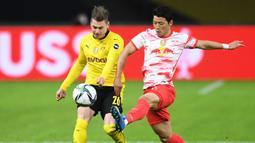 Bek Borussia Dortmund, Lukasz Piszczek (kiri) berebut bola dengan striker RB Leipzig, Hwang Hee-chan dalam laga final DFB Pokal 2020/2021 di Olympiastadion, Berlin, Kamis (13/5/2021). Dortmund menang 4-1 atas Leipzig dan menjadi juara. (AFP/Annegret Hilse/Pool)