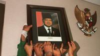 Mahasiswa mencopot foto Presiden Soeharto di gedung parlemen Senayan, Jakarta pada 21 Mei 1998. Soeharto yang telah telah menjadi presiden Indonesia selama 32 tahun mundur setelah runtuhnya dukungan untuk dirinya. KEMAL JUFRI/AFP)