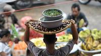 Pedagang membawa cabai di pasar tradisional, Jakarta, Senin (10/10). Kenaikan harga cabai keriting terimbas kondisi cuaca yang kurang baik sehingga membuat pasokan berkurang. (Liputan6.com/Yoppy Renato)