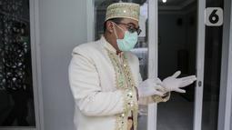 Calon pengantin mengenakan sarung tangan sebelum akad nikah di kawasan Pancoran, Jakarta, Rabu (1/4/2020). Pasangan itu menggelar pernikahan yang hanya dihadiri pihak keluarga mempelai guna menghindari pertemuan dengan orang banyak dan meminimalkan penyebaran COVID-19. (Liputan6.com/Faizal Fanani)