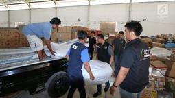 Petugas menurunkan bantuan 4 tenda darurat dan kebutuhan lainnya dari PT Jakarta International Container Terminal (JICT) untuk korban gempa dan tsunami di Palu dan Donggala di Gudang IHC-ACT Parung, Bogor, Jumat (12/10). (Liputan6.com/HO/Arif)