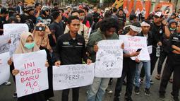 Massa yang tergabung dalam Aliansi Jurnalis Gorontalo membawa sejumlah poster saat menggelar aksi menolak RUU KUHP di Gorontalo, Senin (23/9/2019). Massa terdiri dari AJI, PWI, IJTI, dan beberapa organisasi jurnalis kampus di Gorontalo. (Liputan6.com/Arfandi Ibrahim)