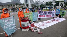 Sejumlah aktivis melakukan teatrikal dengan menyiramkan darah di tubuhnya saat aksi serentak desak Presiden Jokowi deklarasikan Darurat Iklim di kawasan Patung Kuda, Jakarta, Jumat (19/3/2021). Aksi serentak di beberapa lokasi itu untuk menuntut deklarasi darurat iklim. (Liputan6.com/Faizal Fanani)