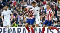 Gelandang Real Madrid, Casemiro, memperebutkan bola dengan penyerang Atletico Madrid, Vitolo, pada laga pekan ke-22 La Liga di Santiago Bernabeu, Sabtu (1/2/2020). (AFP/PIERRE-PHILIPPE MARCOU)