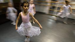 Gadis-gadis kecil mengikuti kelas balet di sebuah studio di Moskow , 22 November 2018. Orang tua dan kakek-nenek duduk di koridor sebuah studio kecil di Moskow utara menunggu anak-anak usia tiga tahun menyelesaikan kelas balet mereka. (Mladen ANTONOV/AFP)