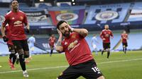 Gelandang Manchester United atau MU Bruno Fernandes berselebrasi usai mencetak gol ke gawang Manchester City dalam lanjutan Liga Inggris di Etihad Stadium, Minggu (7/3/2021).  (Laurence Griffiths/Pool via AP)