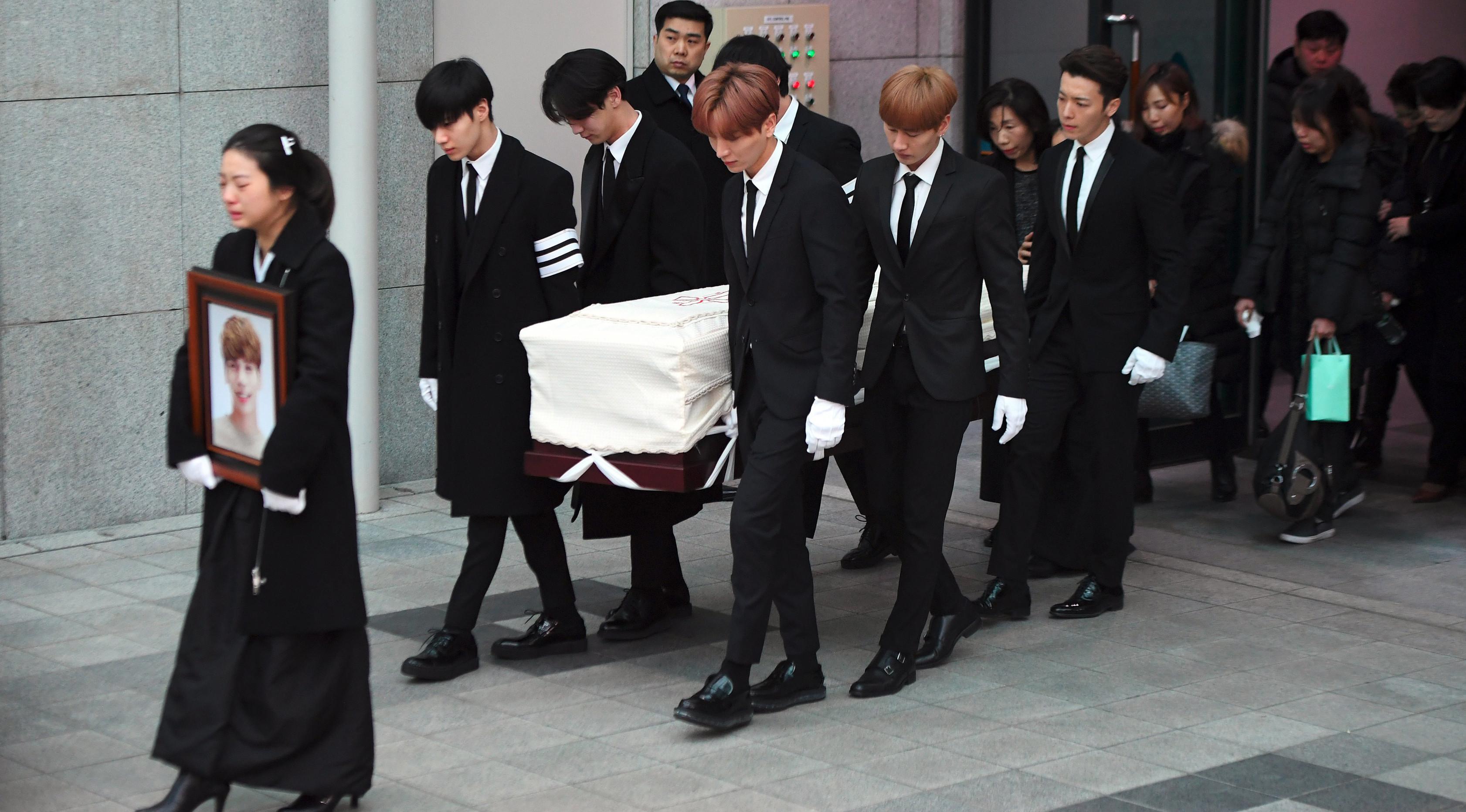 Kakak Jonghyun dan artis SM Entertainment membawa peti mati berisi jenazah Jonghyun (AFP)