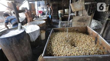 Aktivitas pekerja mengolah kedelai untuk dijadikan tahu di industri rumahan kawasan Duren Tiga, Jakarta, Senin (18/11/2019). Dari data perhitungan Kerangka Sampel Area (KSA) yang diperoleh Kementan, hingga Oktober 2019 produksi kedelai baru mencapai 480 ribu ton. (Liputan6.com/Herman Zakharia)