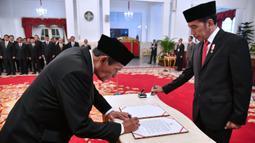 Tumpak Hatorangan Panggabean (kiri) menandatangani nota pelantikan sebagai Dewan Pengawas KPK disaksikan Presiden Joko Widodo di Istana Negara, Jakarta, Jumat (20/12/2019). Upacara pelantikan Dewan Pengawas KPK dipimpin langsung Presiden Joko Widodo. (Foto: Biro Pers Setpres)