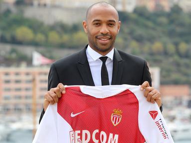 Legenda Prancis, Thierry Henry, memegang jersey saat diperkenalkan sebagai pelatih baru AS Monaco di Monaco, Rabu (17/10). Dirinya menggantikan posisi yang ditinggalkan Leonardo Jardim. (AFP/Valery Hache)