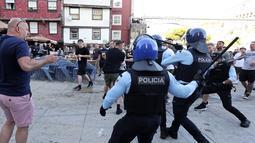 Polisi membubarkan suporter Manchester City yang berkelahi saat minum di tepi sungai Douro di Porto, Portugal (28/5/2021).  Para suporter melanggar jam malam dengan menghabiskan waktu di pub dan bar. (AP Photo/Luis Vieira)