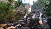 Pencari ikan berdiri di atas bebatuan Curug Cimarinjung, Kawasan Geopark Ciletuh, Sukabumi, Sabtu (23/6). Kawasan yang dikenal sebagai salah satu taman batu tertua di Pulau Jawa ini resmi mendapat predikat UNESCO Global Geopark. (Merdeka.com/Arie Basuki)