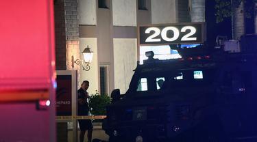 Seorang petugas polisi berdiri di luar gedung perkantoran di mana beberapa orang tewas dalam penembakan di Orange, California (31/3/2021).  Pihak berwenang mengatakan bahwa empat orang, termasuk seorang anak, tewas dalam penembakan dan dua lainnya telah diangkut ke rumah sakit setempat. (AFP/Patrick