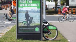 Para pesepeda melintas di depan pos parkir sepeda, Toronto, Kanada, Rabu (2/9/2020). Mulai 2 September, pelanggan layanan penyewaan sepeda Bike Share Toronto dapat menikmati perjalanan gratis di kota tersebut setiap Rabu selama September. (Xinhua/Zou Zheng)