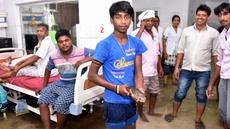 Anggota keluarga pasien yang dirawat, menangkap seekor ikan di dalam bangsal rumah sakit kamar yang tergenang banjir di Nalanda Medical College Hospital, daerah Bihar, India, 29 Juli 2018. Peristiwa unik ini ramai menjadi perbincangan netizen. (AFP PHOTO)