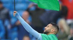 Gelandang Manchester City, Riyad Mahrez mengibarkan bendera Palestina saat merayakan timnya meraih gelar Liga Inggris di stadion Etihad, Minggu (23/5/2021). Pada 10 Mei lalu, Mahrez memposting foto bendera Palestina di akun media sosialnya. (AFP Photo/Pool/Dave Thompson)