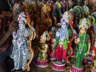 Seorang seniman India mewarnai patung dewa Hindu Rama di sebuah lokakarya di Hyderabad, India (15/3). Para seniman ini membuat patung dewa menjelang festival Rama Navami. (AFP/Noah Seelam)
