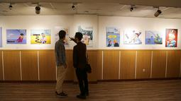"Pengunjung melihat karikatur seniman Iran  yang menampilkan Ratu Elizabeth II Inggris sebagai ""bajak laut""  di Teheran (30/7/2019). Hubungan tegang antara Teheran dan London memburuk ketika Angkatan Laut Kerajaan Inggris menyita kapal tanker minyak ""Grace 1"" Iran pada 4 Juli. (AFP Photo/Atta Kenare)"