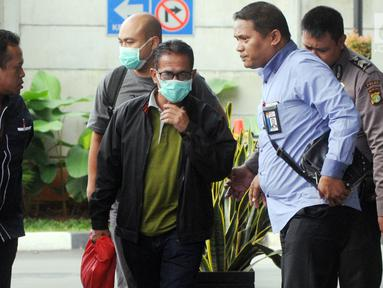 Bupati Mesuji Khamami (tengah) tiba di Gedung KPK, Jakarta, Kamis (24/1). Khamami menutupi wajahnya menggunakan masker. (Merdeka.com/Dwi Narwoko)