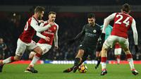 Striker Manchester City, Sergio Aguero dikepung pemain Arsenal Shkodran Mustafi, Welsh Aaron Ramsey dan Hector Bellerin pada laga pekan ke-28 Premier League di Emirates Stadium,  Jumat (2/3). Manchester City mempermalukan Arsenal 3-0. (Glyn KIRK/AFP)