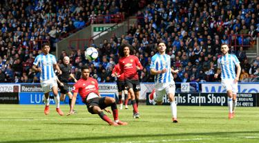 Penyerang Manchester United, Marcus Rashford terpeleset ketika berusaha melakukan tendangan ke gawang Huddersfield Town pada pekan ke-37 Liga Inggris di John Smith's Stadium, Minggu (5/5/2019). MU gagal ke Liga Champions musim depan setelah ditahan Huddersfield Town 1-1. (Anthony Devlin/PA via AP)
