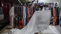 Pedagang merapikan kain di pusat penjualan pakaian dan tekstil Pasar Tanah Abang Blok B, Jakarta, Selasa (19/1/2021). Produksi pakaian diprediksi akan membaik pada posisi 3,75 persen pada tahun ini. (Liputan6.com/Johan Tallo)