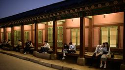Gambar pada 4 Oktober 2019, wisatawan duduk di bangku dekat halaman saat kunjungan malam ke Istana Gyeongbokgung di Seoul, Korea Selatan. Kunjungan malam tersedia pada minggu ketiga dan keempat setiap bulan mulai dari 26 April sampai 31 Oktober, kecuali pada bulan Agustus. (Photo by Ed JONES / AFP)