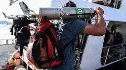 Penyelam membawa tangki oksigen untuk melanjutkan pencarian korban kapal wisata yang terbalik di dermaga Chalong, Phuket, Sabtu (7/7). Kapal Phoenix diketahui dihantam gelombang setinggi lima meter saat badai Kamis malam. (AFP/Mohd RASFAN)