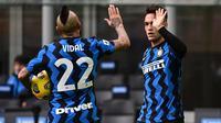 Striker Inter Milan, Lautaro Martinez (kanan) berselebrasi dengan Arturo Vidal pada laga melawan Crotone, di Giuseppe-Meazza, Minggu (3/1/2021). (AFP/Miguel Medina)