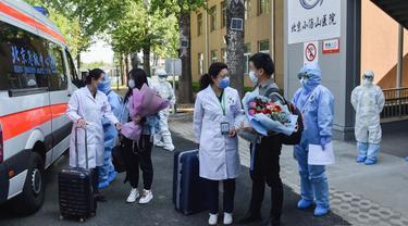 Staf medis mengucapkan selamat jalan ke pasien sembuh COVID-19 di Beijing, China (28/4/2020). Rumah Sakit Xiaotangshan yang digunakan untuk mengarantina pasien SARS di Beijing, telah memulangkan semua pasien COVID-19 Selasa (28/4) dan dijadwalkan berhenti beroperasi Rabu (29/4). (Xinhua/Peng Ziyang)