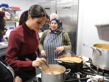 Duchess of Sussex Meghan Markle memasak bersama komunitas Hubb Community Kitchen di London, Inggris (21/11). Kegiatan Istri Pangeran Harry itu untuk melakukan proyek amal. (Chris Jackson/Pool via AP)